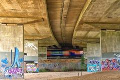Speeding train passes through graffiti covered bridge supports, under the M25 motorway. royalty free stock photography