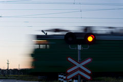 Speeding train passing a level crossing Royalty Free Stock Photo