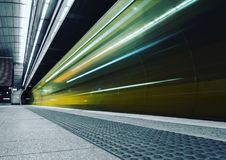 Speeding train. Transportation subway train speeding past tact tiles like trails train station underground modern transportation public transport commuting Stock Image