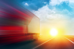 Speeding Transportation Delivery Truck on Open Highway. With Sun Settimg Down on Horizon in Background Stock Image