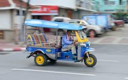 Speeding Tuk Tuk in Bangkok. Smiling Driver waving his hands in a Speeding Tuk Tuk Taxi in China Town, Bangkok Stock Image