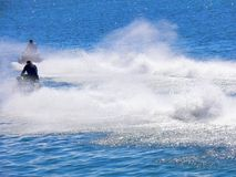 Speeding Water Scooters. Two water scooters roaring across the sea Royalty Free Stock Image