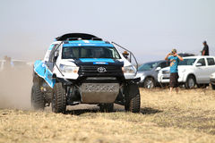 Speeding white and blue Toyota Hilux twin cab rally car front vi. Sun City, South Africa – OCTOBER 1, 2016: Front view of Speeding white and blue Toyota stock photography