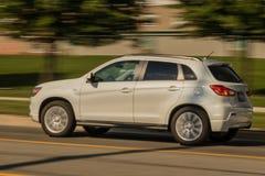 Speeding white SUV in motion stock photography