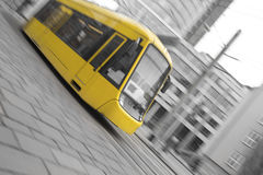 speeding yellow tram with black and white city background Stock Photos
