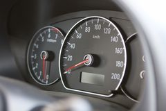 Speedometer. A closeup of a car dashboard with a speedometer in focus and a tachometer slightly out of depth of field Stock Image
