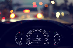Speedometer in modern vehicle car drive travel road trip. In night city with blur bokeh traffic light on street background Stock Photography