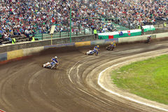 Speedway. Four speedway racers on the racetrack and spectacors Royalty Free Stock Images