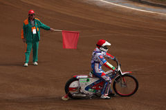 Speedway riders compete on track in Pardubice, Czech Republic. PARDUBICE, CZECH REPUBLIC - OCTOBER 14, 2012: Race referee waves the red flag to a speedway rider royalty free stock photography