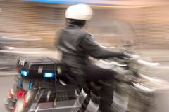 Speedy Cop. A motorcycle cop speeds by in hot pursuit of a car. The long shutter speed is intentional, and conveys motion and action royalty free stock photography