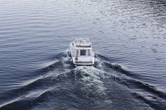 Speedy luxury white motor boat on the water surface. Transport Stock Image