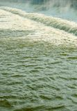 Speedy river water from the dam texture background with bubbles. Royalty Free Stock Photos