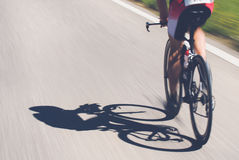 Speedy shadow. A cyclist at top speed on the triathlon race Stock Photography
