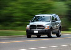 Speedy SUV. Silver SUV in motion. 3/4 front angle shot with blurred background stock photos