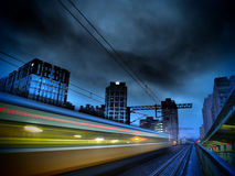 Speedy Train and Modern City at night Royalty Free Stock Images
