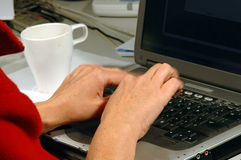 Speedy Typist. Hands fast typing on a laptop - focus is on the hands and the fingers have motion blur Royalty Free Stock Photos