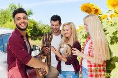 Speel de gitaarvrienden die van de jongeren luisterkerel het openluchtplatteland van bierflessen drinken Stock Foto's