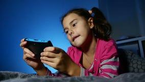 Speel het jonge geitje draagbaar video online spel van het tienermeisje een consolejong geitje bij nacht binnen stock videobeelden