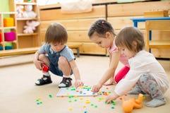 Speel het mozaïekspel van de jonge geitjesgroep in kleuterschool stock afbeeldingen