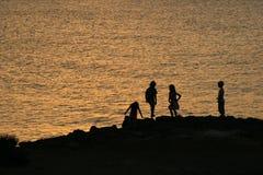 Speel kinderen bij het overzees/het silhouet Stock Foto