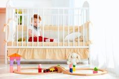 Speelgoed op de vloer in zonnige slaapkamer met zuigelingsbaby in de voederbak op achtergrond stock fotografie