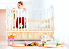 Speelgoed op de vloer in zonnige slaapkamer met zuigelingsbaby in de voederbak op achtergrond stock foto