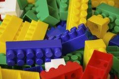 Speelgoedinzameling op witte achtergrond wordt geïsoleerd die Multi gekleurde plastic aannemer met blokken voor de bouw van huize royalty-vrije stock fotografie