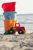 Speelgoedkinderen voor het strand op het zand Overzees en hemel op de achtergrond Stock Afbeelding