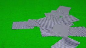 Speelkaarten die op groene lijst vallen stock videobeelden