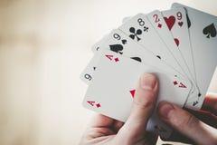 Speelkaarten: Pookkaarten in de hand van een jonge mens stock foto