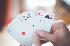 Speelkaarten: Pookkaarten in de hand van een jonge mens stock afbeeldingen