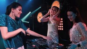 Speelmuziek van de drie het glimlachen de jonge meisjesband op draaischijven en het zingen liederen DJ met draaischijven en blond stock videobeelden