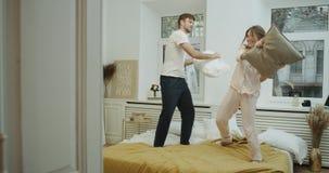 Speelpaar met twee kussens in bed in de zeer romantische ochtend, zij dragen pyjama's stock videobeelden