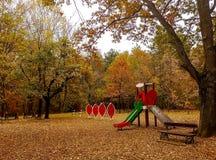 Speelplaats in het park met bos wordt omringd dat stock afbeelding