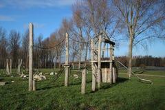 Speelplaats met verscheidene hulpmiddelen van het waterspel en trekkrachtveerboot over sloot in het openbare park Hitland in het  stock fotografie