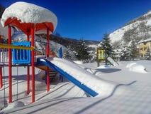 Speelplaats onder sneeuwdekking stock fotografie