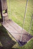 Speelplaatsschommeling het hangen op groen grasgebied Stock Foto