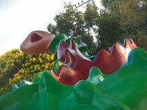 Speelplaatsstandbeeld van een slangdinosaurus voor jonge geitjes in een stedelijk park met bloeiende bomen op de achtergrond royalty-vrije stock foto