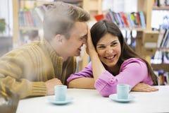 Speels jong paar met koffiekoppen op bureau in bibliotheek Stock Foto's