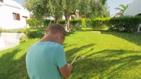 Speels kind die groen gazon water geven door het huis stock video