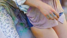 Speels meisje die met mens flirten, die in kleurrijk poeder bij Holi-festival de dansen stock footage