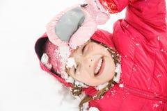 Speels meisje die met vlechten in de eerste sneeuw spelen royalty-vrije stock fotografie
