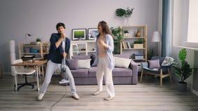 Speels paar die pret met stofzuiger hebben die genietend van vrije tijd dansen stock video