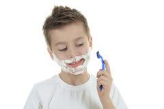 Speels weinig jong jongen het scheren gezicht over wit Stock Foto's