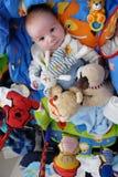 Speelse baby die door speelgoed wordt omringd stock afbeeldingen