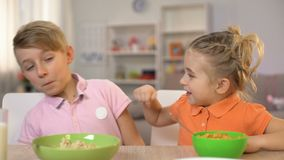 Speelse broer en zuster wat betreft neus elkaar, die pret hebben tijdens ontbijt stock video
