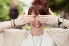 Speelse Dame Covering haar Ogen die haar Handen gebruiken royalty-vrije stock fotografie