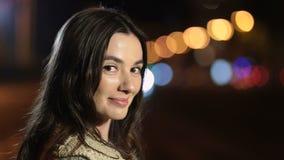 Speelse glimlachende vrouw die op straat bij nacht flirten stock footage
