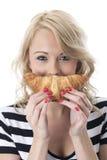 Speelse Jonge Vrouw die een Ontbijtcroissant houden royalty-vrije stock foto's