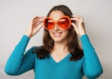 Speelse jonge vrouw met grote partijglazen Stock Fotografie